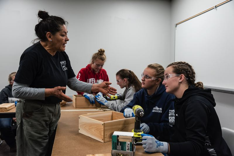 PHOTOS: MELISSATOLEDO.COM, COURTESY OREGON TRADESWOMEN - (L-R) Mayella Alverado of the ReBuilding Center, helps Kari Robbins and her friend Taylor Davis, both juniors at Pleasant Hill High School outside of Eugene, make a planter. The girls say they will probably both go into the family businesses: electrical work for Robbins, the Navy for Davis.