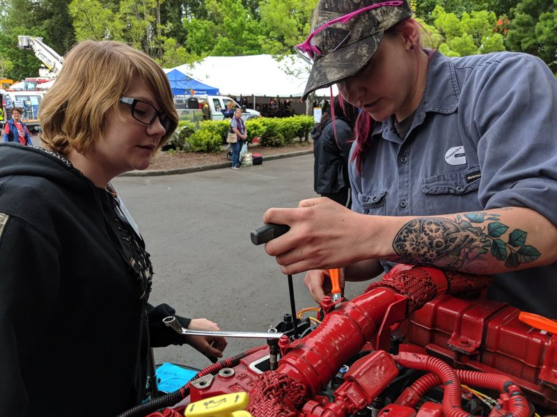 PAMPLIN MEDIA GROUP: JOSEPH GALLIVAN  - At the Oregon Tradeswomens Career Fair girls could try tuning a diesel engine (Emma Flanagan looks on as Cummins mechanic Angeline DeLuca demonstrates.