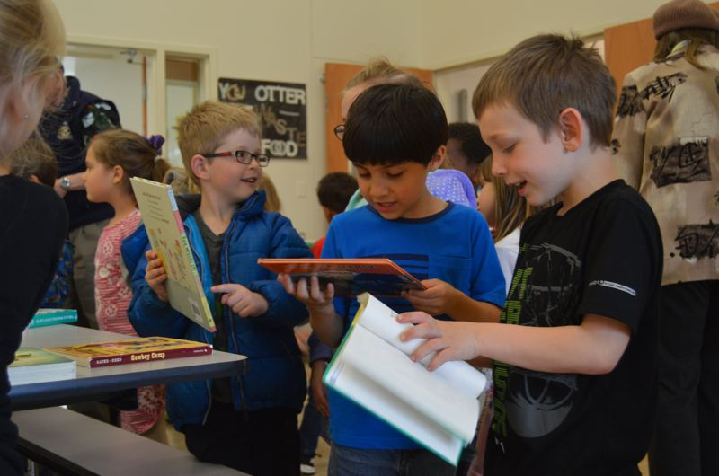 SPOTLIGHT PHOTO: NICOLE THILL-PACHECO - Students at Columbia City Elementary School look at books they received on May 18.