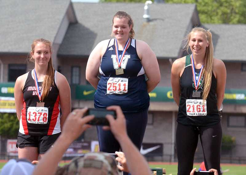 SPOKESMAN PHOTO: TANNER RUSS - Maggie Woginrich stands at the top of the awards podium with a first place medal around her neck. She will be a college athlete next spring season at Northwest Christian University.