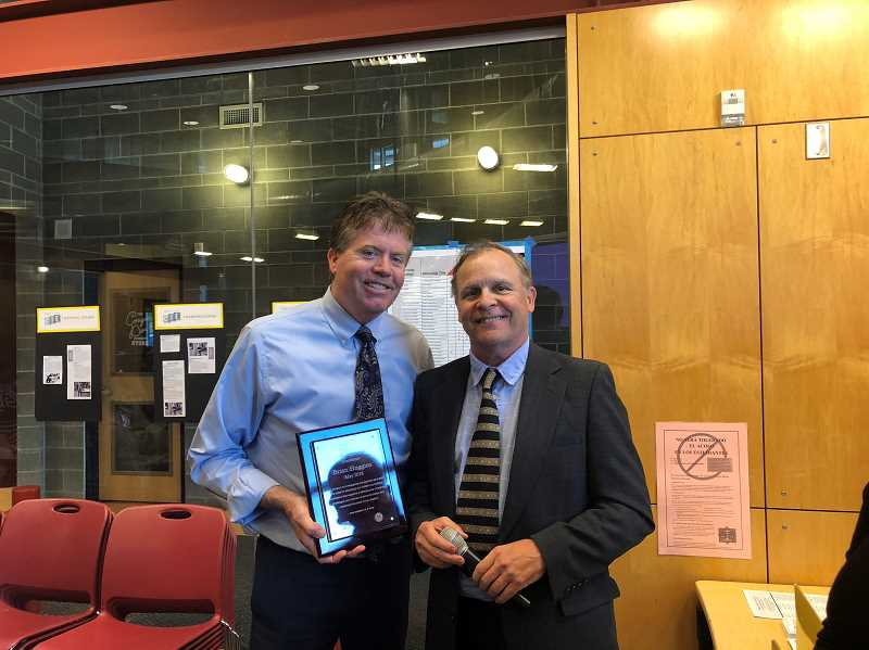 COURTESY PHOTO: CANBY SCHOOL DISTRICT - Brian Huggins (left) receives the CARE Award from Superintendent Trip Goodall.