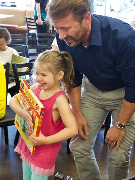 OUTLOOK PHOTO: CHRISTOPHER KEIZUR - One of the students from KinderCare showed off the book she picked out from the Gresham Reads case at Biscuits Café.