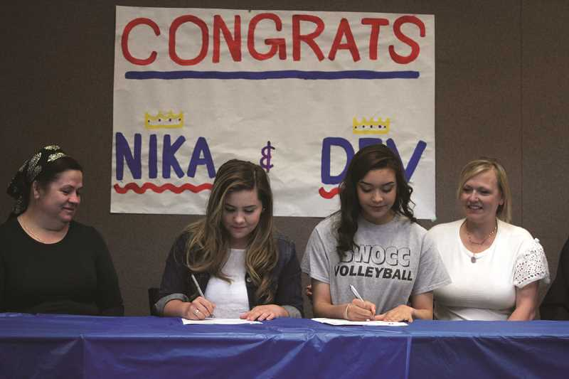 PHIL HAWKINS - Woodburn seniors Domnika Krivoshein (left) and Devanee Ott-Parker sign their letters of intent to continue their volleyball careers at Southwest Oregon Community College in Coos Bay this fall.