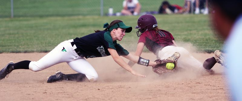 DAN BROOD - Tigard junior shortstop Maddie Hoover (left) dives in an attempt to tag out Glencoe's Mordan DeBord on a stolen-base attempt.