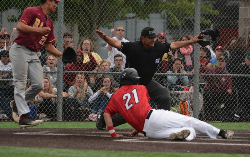 OUTLOOK PHOTO: DAVID BALL - The umpire rules Clackamas senior Greg Mehlhaff safe at home after scoring on a wild pitch for the go-ahead run in the third inning.
