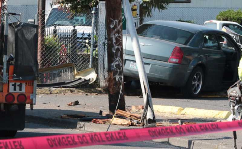 DAVID F. ASHTON - Workers at shops nearby said they're surprised no one was killed, when this Chrysler left the street and smashed right through a utility pole.