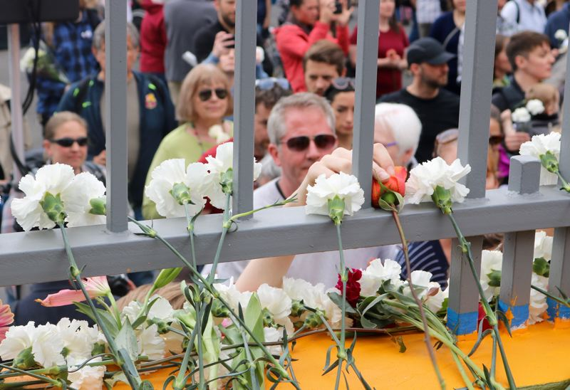 TRIBUNE PHOTO: ZANE SPARLING - Hundreds of white carnations and other flowers were placed on the Hollywood Transit Center walkway during a tribute on Saturday, May 26 in Portland.