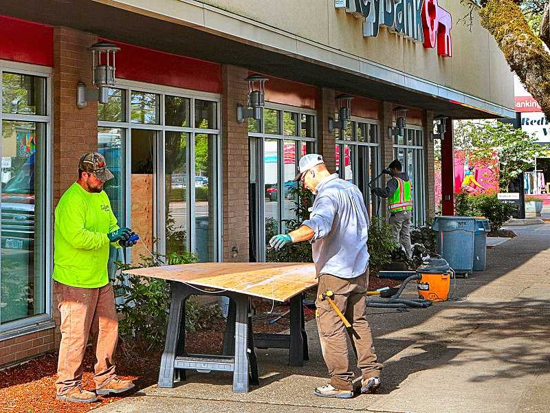 DAVID F. ASHTON - Before it could open for the day on May 2, workers were replacing shattered plate glass windows at the Woodstock KeyBank branch.
