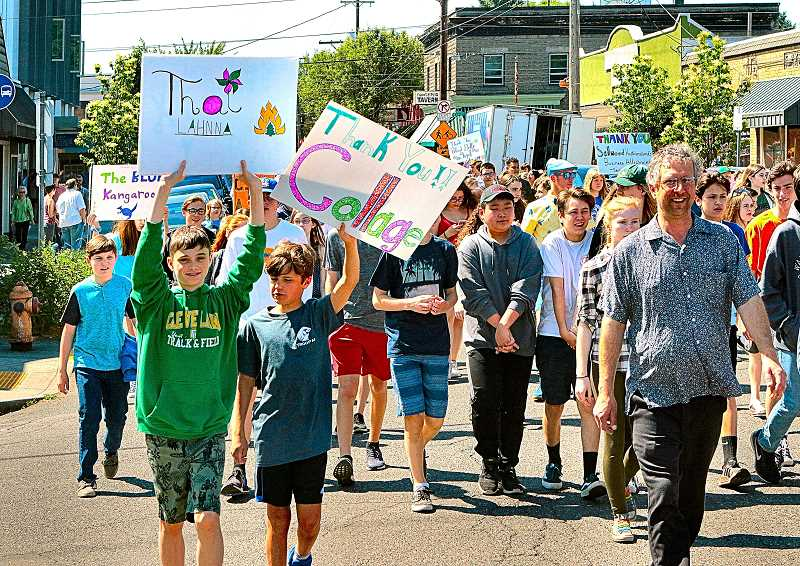 DAVID F. ASHTON - Before the parade, Sellwood Middle School students made thank you cards for local businesses which they displayed during the parade - here, they were marching through the Sellwood business district.