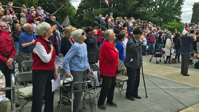 TIMES PHOTO: DANA HAYNES - Standing for the presentation of the American flag, plus a flyover of twin F-15 fighter jets, during Monday's Memorial Day celebration in Beaverton.