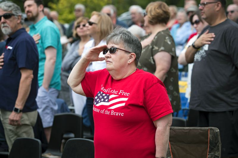 TIMES PHOTO: JAIME VALDEZ - Cheryl Hoskins salutes the American Flag as the Tualatin Police Honor Guard Posts the Colors during the Memorial Day program at Winoma Cemetery.