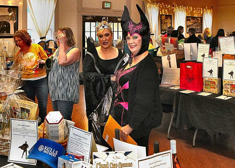 DAVID F. ASHTON - These costumed characters - Llewellyn Dinner Auction volunteers Jeanne Ballaris and Tamara Pugh - check bids during the silent auction.