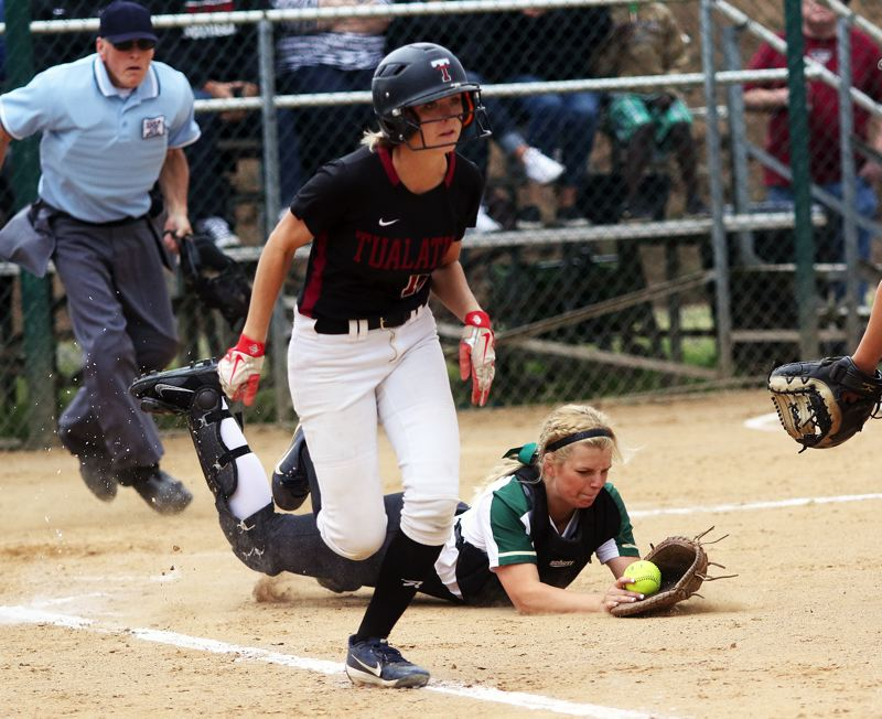DAN BROOD - Tualatin senior Ella Hillier sprints to first base, as Jesuit senior catcher Annalisa Williamson dives to grab Hillier's bunt on the bounce during Friday's state playoff quarterfinal game.