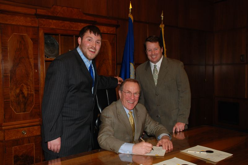 COURTESY PHOTO - Lawyer David Kracke and Max Conradt joined Gov. Ted Kulongoski at the signing the new law protecting young athletes.