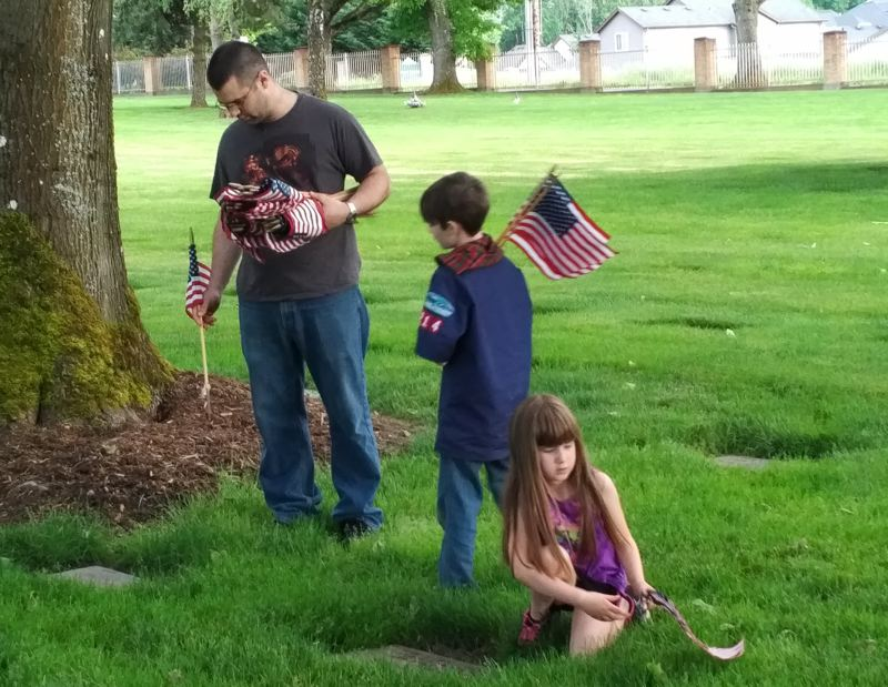 CONTRIBUTED PHOTO: JEFF REYNOLDS - Marc Tibbetts carries a handful of flags for his son Nick, during the Boy Scouts annual flag plant at Willamette National Cemetery.