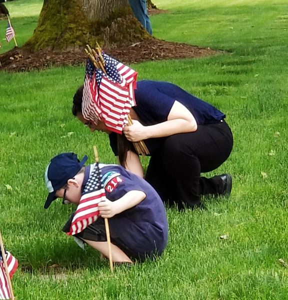 CONTRIBUTED PHOTO: JEFF REYNOLDS - Kadance Mahan from Cub Scout Pack 214 in Rockwood and a member of his family read the name of the buried veteran before planting a flag above the headstone.