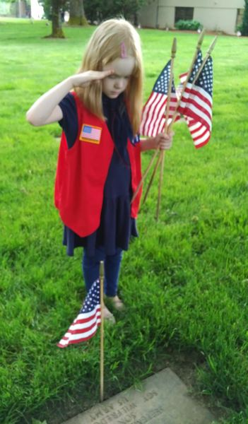 CONTRIBUTED PHOTO: JEFF REYNOLDS - Tate Reynolds, a member of American Heritage Girls Troop 0613, salutes a veteran buried at Willamette National Cemetery before placing a flag on the grave.