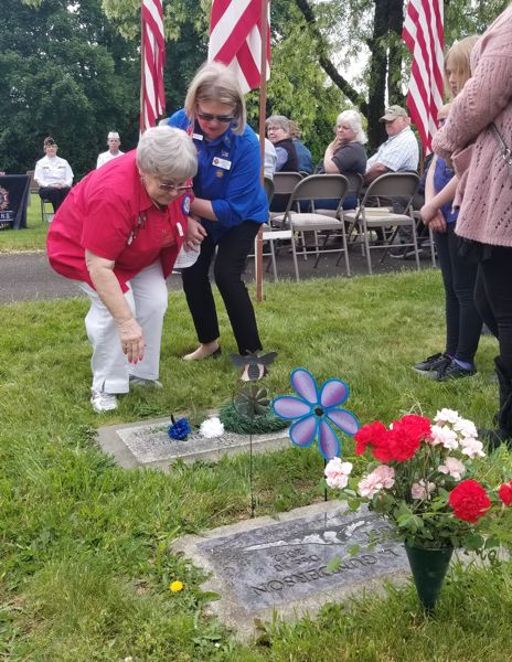 SANDY POST: STEVEN BROWN - JoAn Gunderson lays a flower on the grave of her husband, Alan Gunderson, who lived his entire life in Sandy except the four years he served in the U.S. Navy during the Korean War. He died in 2012.  JoAn Gunderson is joined in this photo by Voriece Blair, president of the Sandy VFW Auxiliary.