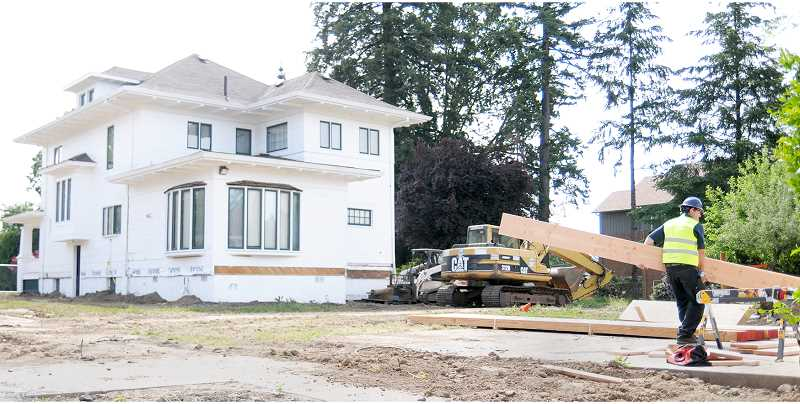 ALICIA WOLVERTON - Workers prepare the Villa Road House for transport on Sunday to its new home near the intersection of Meridian and Sheridan streets.