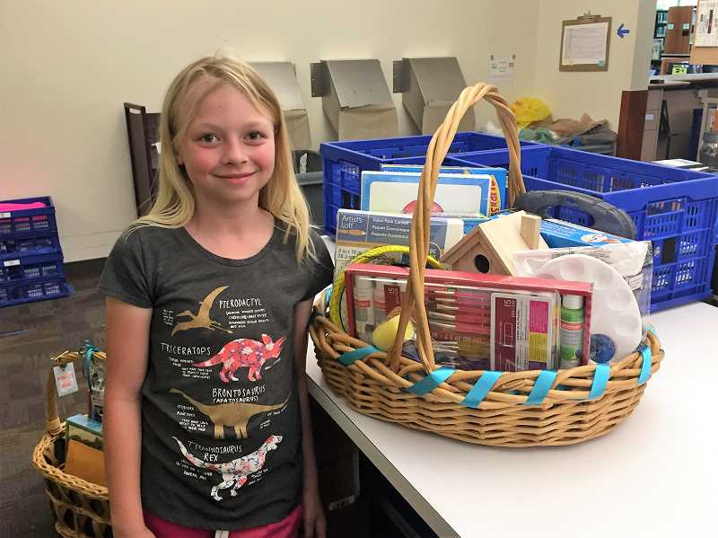ESTACADA NEWS PHOTO: EMILY LINDSTRAND - Alexis Hibbert, 9, stands next to the gift basket she put together with her mother, Estacada Public Library Circulation Manager Sarah Hibbert. The basket is one of several that will be raffle prizes for the librarys summer reading program.