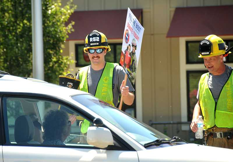 SPOKESMAN PHOTOS: VERN UYETAKE - Firefighters Andrew Erks, left, and Jon Bullock chat with a motorist making a donation on Wilsonvillle Road.