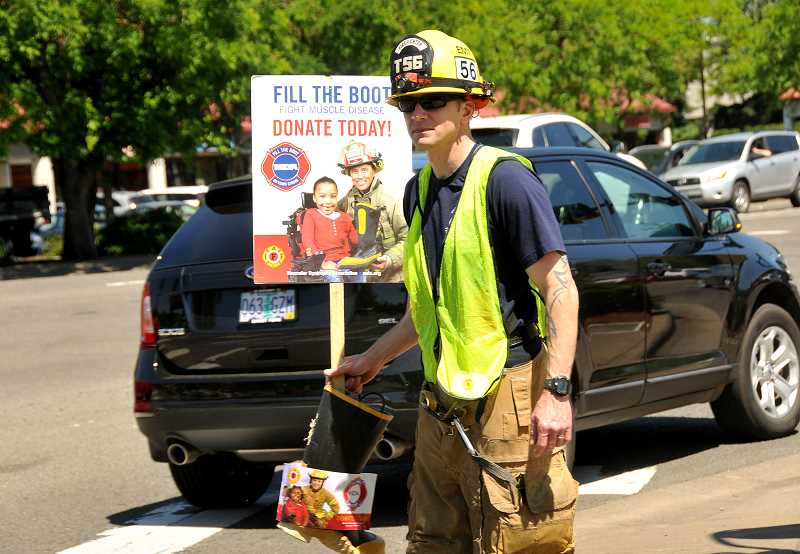 SPOKESMAN PHOTO: VERN UYETAKE - Firefighter Justin Speasl stands ready for donations along Boones Ferry Road.