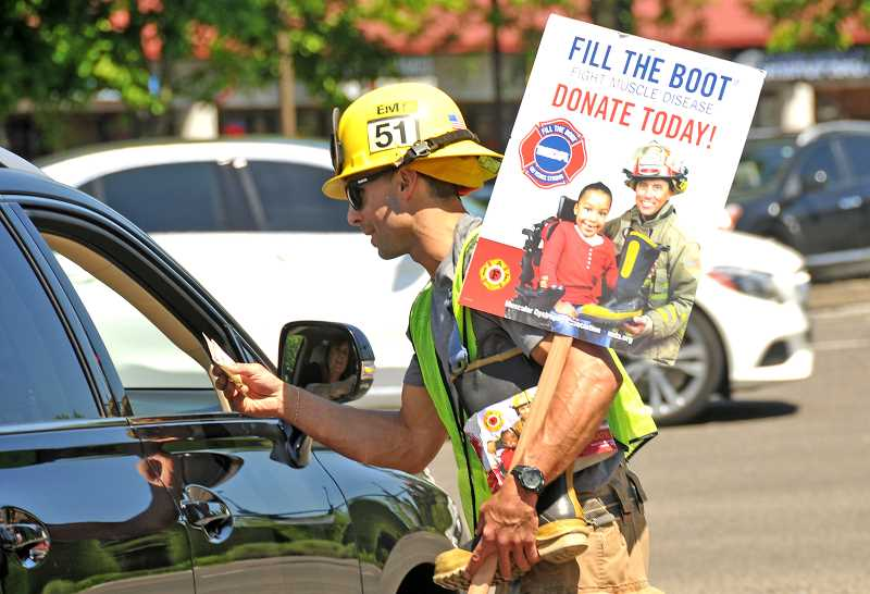 SPOKESMAN PHOTO: VERN UYETAKE - Firefighter Justin Speasl collects a donation from a passing motorist.