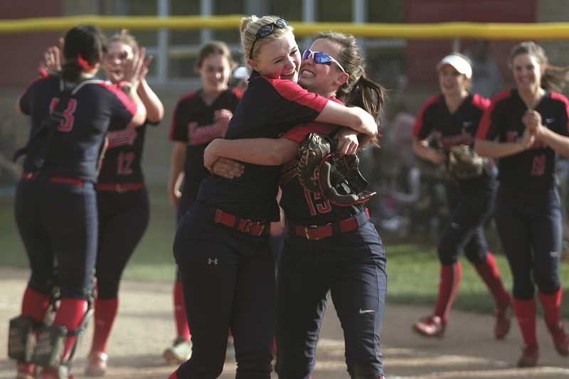 PHIL HAWKINS - Kennedy senior Molly Jaeger (left) embraces freshman Hailey Arritola after the Trojans beat Central Linn 10-1 on Tuesday. The pair are making their second state championship appearance this year after playing as teammates on the 2A State Champion girls basketball team in March.
