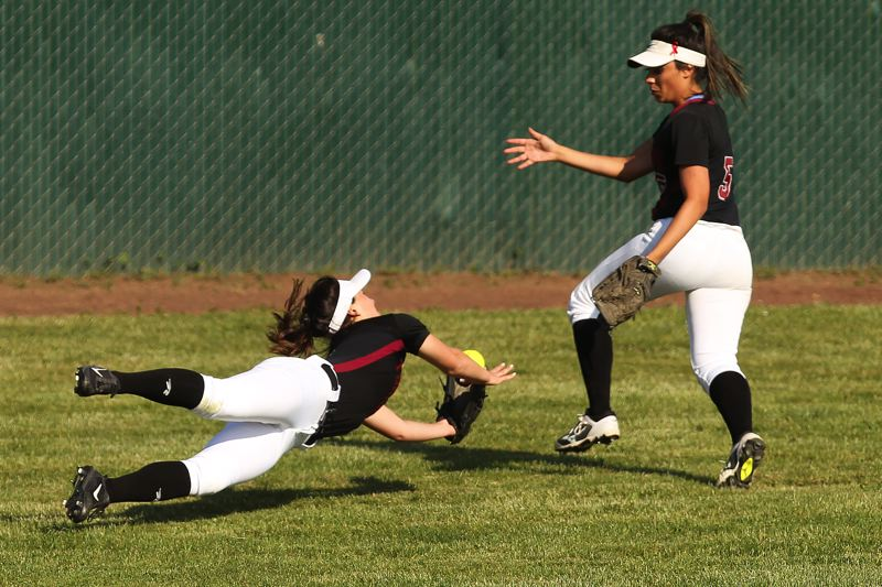 TIMES PHOTO: JAIME VALDEZ - Tualatin junior left fielder Lily Marshall (left) dives for the ball during the win over West Salem.