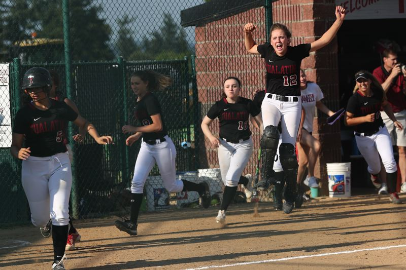 TIMES PHOTO: JAIME VALDEZ - Tualatin senior Ella Hillier (12) jumps in the air following Emily Johansen's home run.