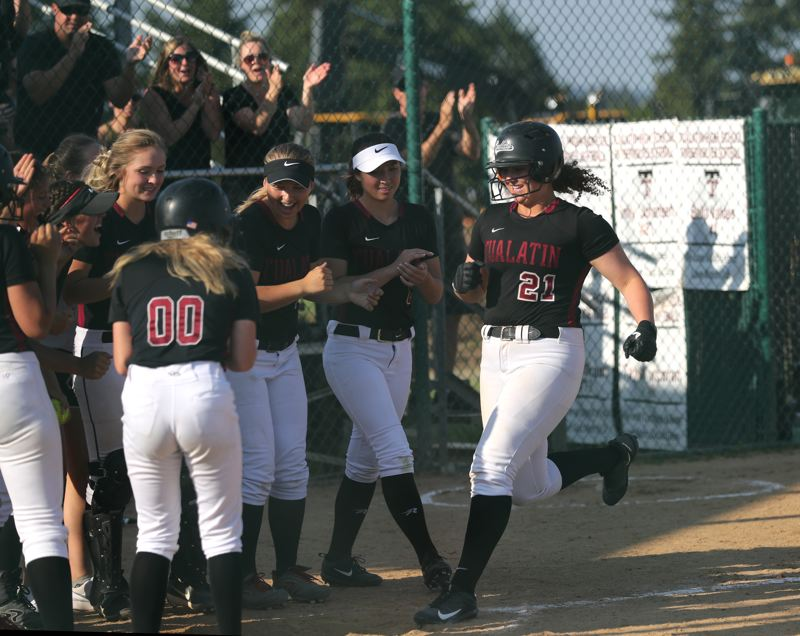 TIMES PHOTO: JAIME VALDEZ - Tualatin junior Emily Johansen (21) is met by her teammates at home plate following her home run against West Salem.