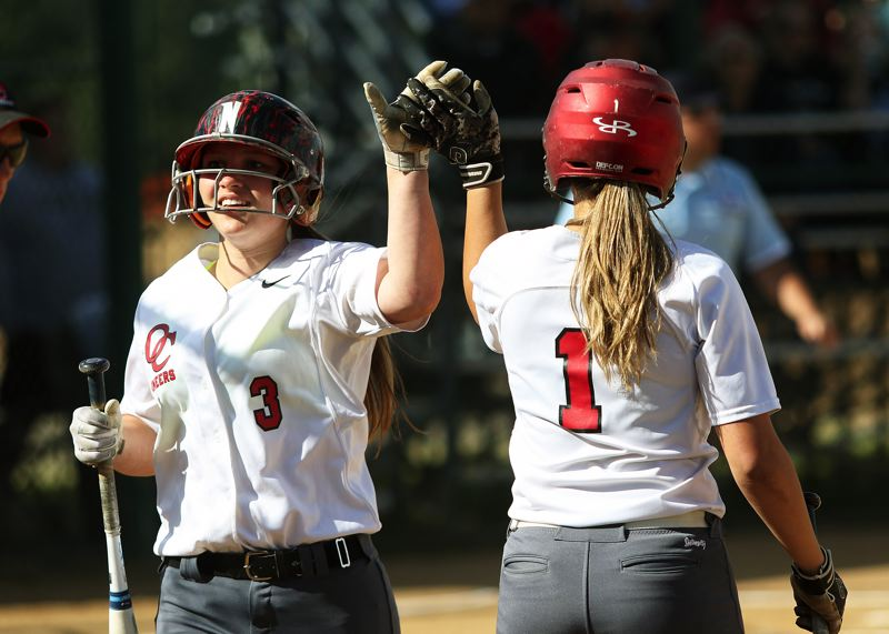 TIMES PHOTO: DAN BROOD - Oregon City's Aliyah Kelly (left) is congratulated by Jordyn Duntley after scoring a first-inning run in Tuesday's state playoff semifinal game at Tualatin.