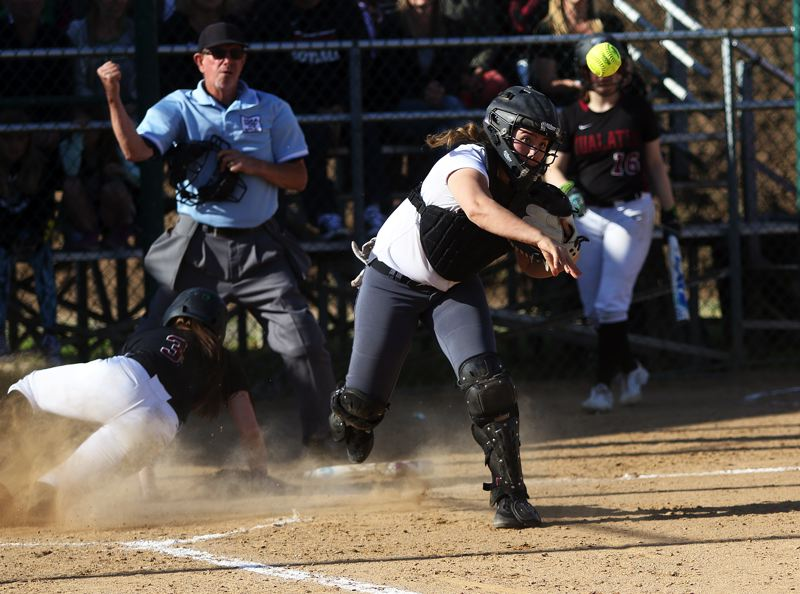 TIMES PHOTO: DAN BROOD - Oregon City sophomore catcher Isabelle Lewis makes a throw to first base after forcing out Tualatin senior Taylor Alton at the plate.