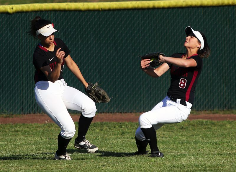 TIMES PHOTO: DAN BROOD - Tualatin junior right fielder Lily Marshall (right), with senior center fielder Zoe Olivera next to her, catches a fly ball during Tuesday's state playoff semifinal game.