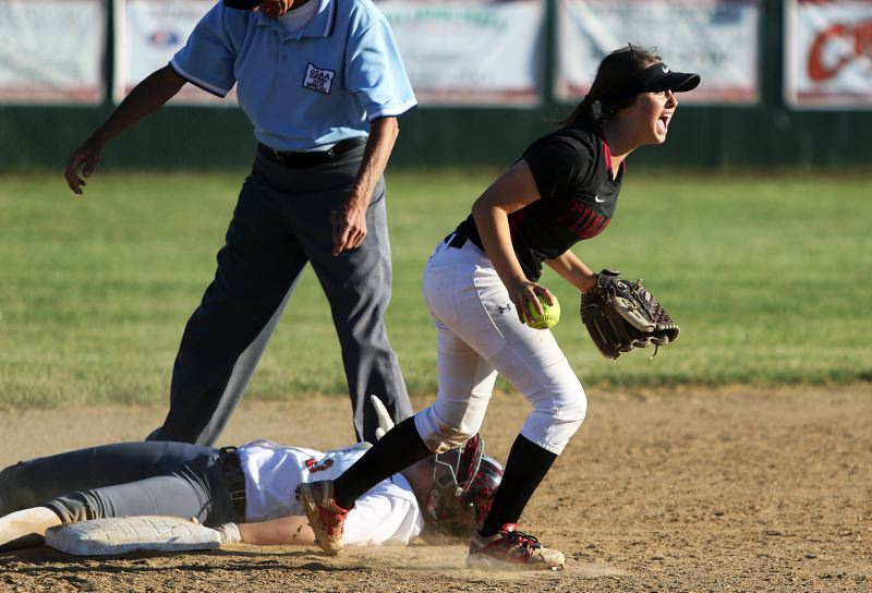 TIMES PHOTO: DAN BROOD - Tualatin sophomore shortstop Bella Valdes lets out a yell after tagging out Oregon City's Aliyah Kelly on a stolen base attempt during the seventh inning of Tuesday's semifinal game.