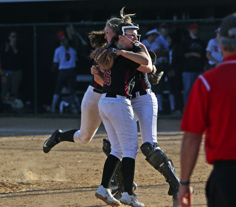 TIMES PHOTO: DAN BROOD - Tualatin seniors Megan Woodward and Ella Hillier share a hug following the Wolves 8-5 state playoff semifinal win over Oregon City.