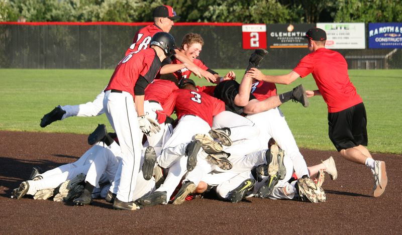 PAMPLIN MEDIA: JIM BESEDA - Clackamas players pig pile on top of senior cathcer Jake Zehr after his grounder pushed home Ryan Ahlstrom with the deciding run in Tuesday's 3-2 semifinal win over South Salem.