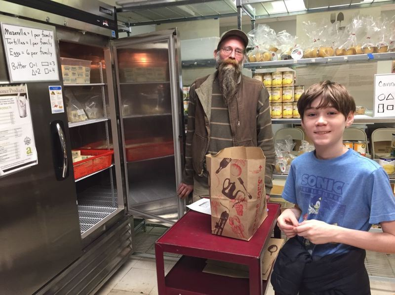 PHOTO COURTESY: LESLIE ROBINETTE - A sixth-grade student at Kraxberger Middle School, Colton Wilson (right) volunteers at the Gladstone Food Pantry to help an unnamed customer choose foods.