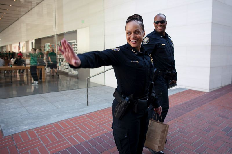 TRIBUNE PHOTO BY JAIME VALDEZ - Chief Danielle Outlaw waves to someone in downtown Portland as she heads to City Hall to meet with Mayor Ted Wheeler, accompanied by Adjutant Sgt. Chuck Lovell.