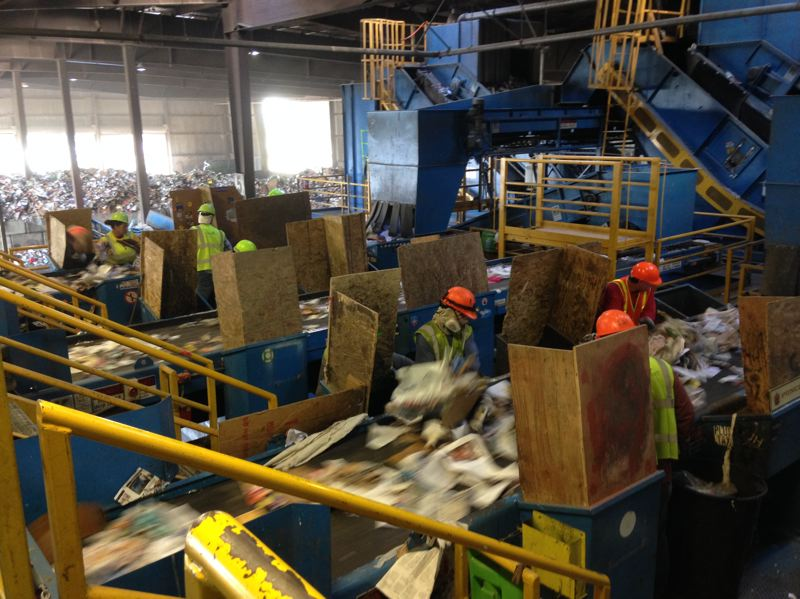 PHOTO COURTESY OF KATHY BOUTIN-PASTERZ - Workers at a material recycling facility sort recycled items thrown on a conveyor belt, to pick out garbage that doesn't belong.