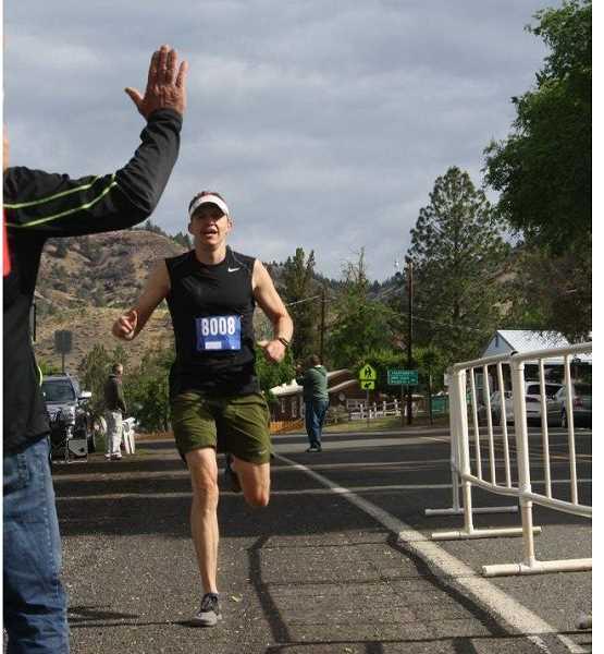 PHOTO COURTESY OF JOHN WAGNER - Brandon Brasher receives a high five as he crosses the finish line in first place at the Eastern Oregon Half Marathon.