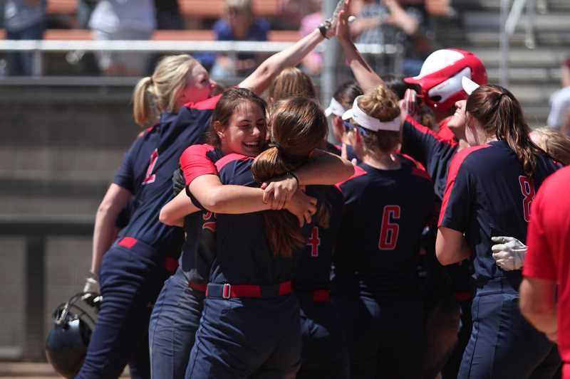 PHIL HAWKINS - The Kennedy softball team celebrates its first state title in program history moments after scoring the winning run in a 10-0 victory over the Pilot Rock Rockets on Friday.