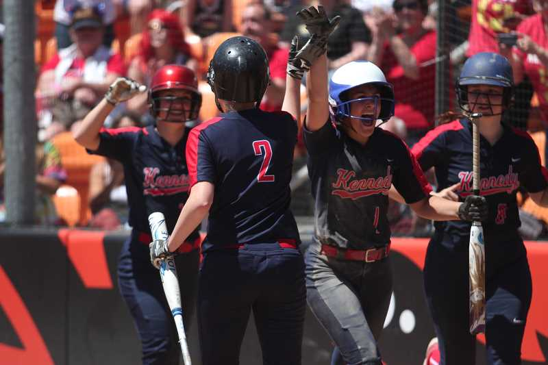PHIL HAWKINS - Kennedy's Elise Suing (left), Kelsey Kleinschmit (middle right) and Rylie Newton (right) celebrate with Molly Jaeger (middle left) after all three scored on a bases-loaded double from teammate Hailey Arritola.