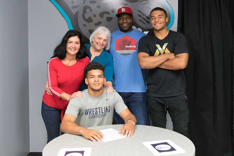 STAFF PHOTO: CHRISTOPHER OERTELL - Century senior Josh Grant signs his letter of intent to wrestle at California Baptist University with his mother Kimberlee Grant, grandmother Sandi Normoyle, his father Leroy Grant and his brother Jamarcus Grant at Century High School in Hillsboro, Ore., on Wednesday, May 30, 2018.