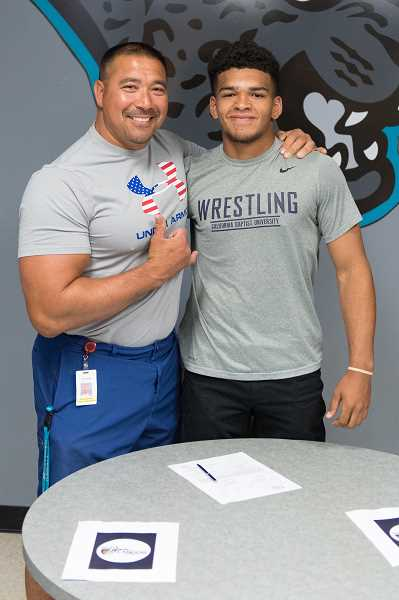 STAFF PHOTO: CHRISTOPHER OERTELL - Century's Josh Grant poses for a photo with Century wrestling coach Guy Takahashi at his letter of intent ceremony May 30, at Century High School.