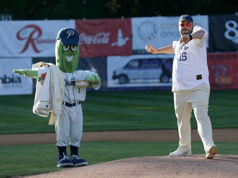 TRIBUNE PHOTO: JONATHAN HOUSE - As mascot Dillon observes, Royal Rosarian prime minister Adam Baker throws out the first pitch to start the Portland Pickles' 2018 season at Walker Stadium on Friday night.