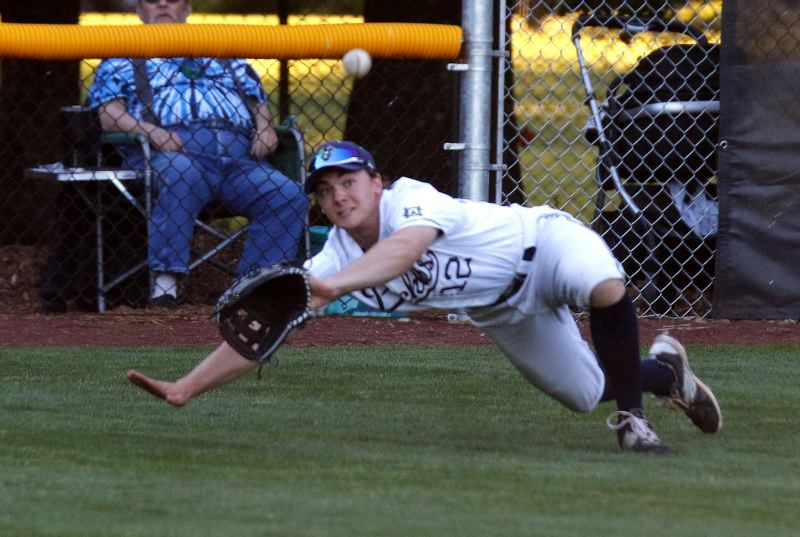 TRIBUNE PHOTO: JONATHAN HOUSE - Gabe Skoro, a former Lincoln High star and current University of Portland player, dives for a ball in left field as the Portland Pickles opened their West Coast League season on Friday night.