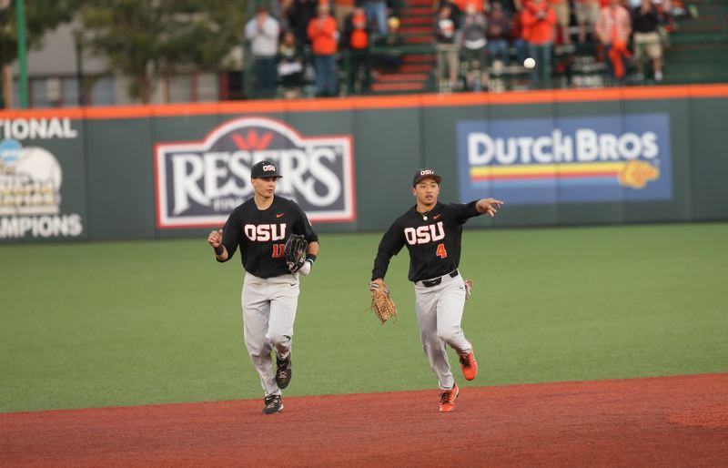 TRIBUNE PHOTO: SCOTT CASSIDY - Trevor Larnach (left) and Steven Kwan of Oregon State celebrate Kwan's standout catch in the outfield on the way back to the dugout Saturday against LSU.