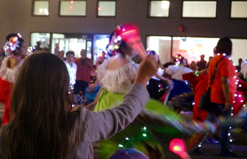 TRIBUNE PHOTO: ZANE SPARLING - A girl waves a flashing baton as illuminated dancers twirl by during the 2018 Starlight Parade on Saturday, June 2 in downtown Portland.