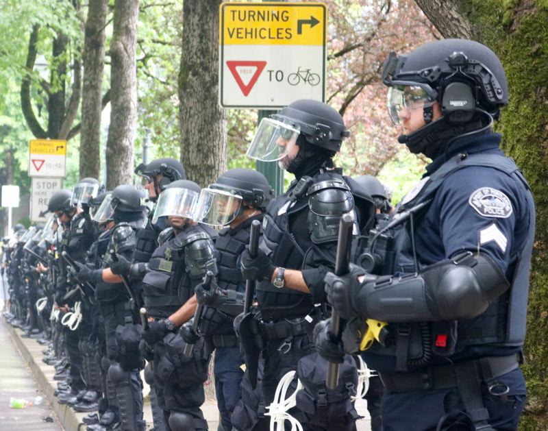 TRIBUNE PHOTO: ZANE SPARLING - Riot police officers line Southwest Madison Street on Sunday, June 3 in Portland.